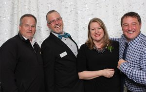 NorthAmericaTalk CEO Dan Jones (right) and VP of Sales Martin McElliott (left) celebrate an award with WhatcomTalk teammates Kevin Coleman (in bow tie) and Stacee Sledge.
